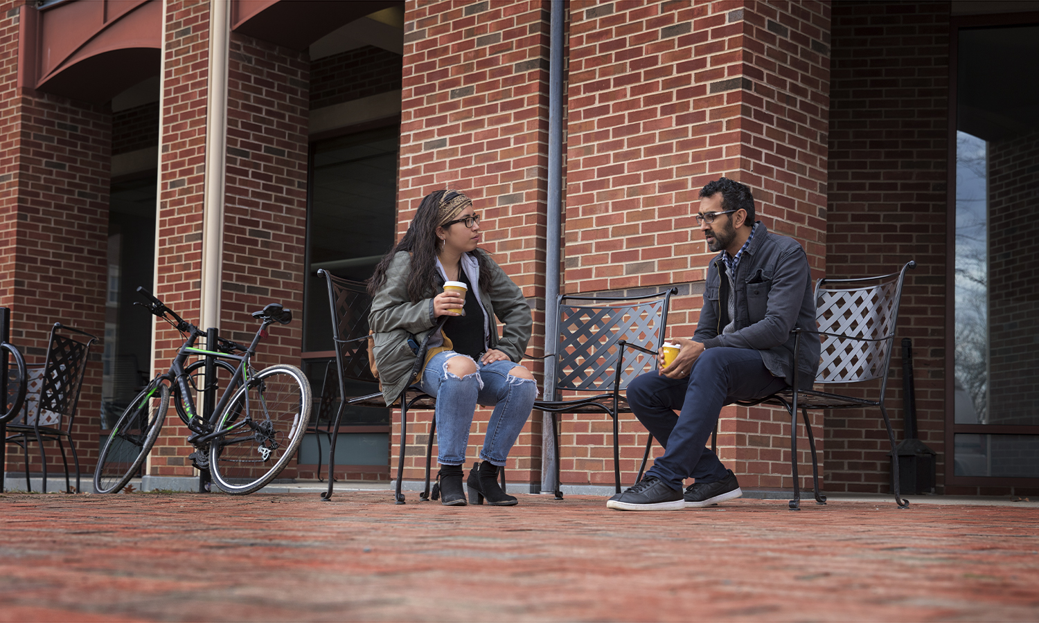 Nathalie Reyes-Madrid '20 chats with Associate Professor of Education Khuram Hussain on the Warren Hunting Smith Library Patio.