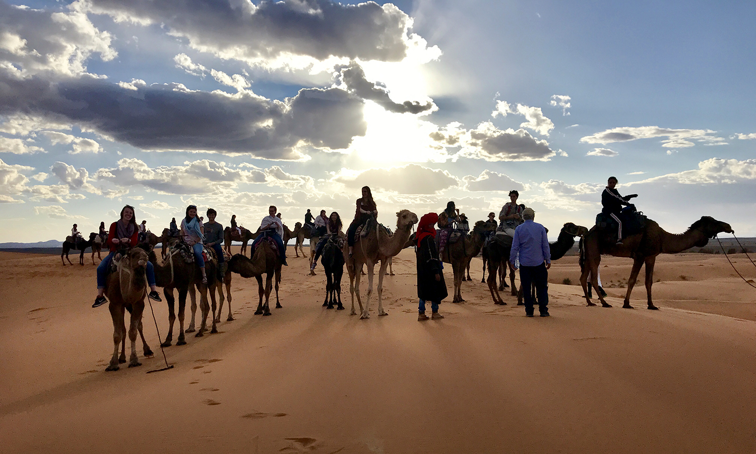Carly Kelly '20 rides a camel in the Sahara desert alongside  guides and other students studying abroad in Morocco through the HWS Center for Education and the School for International Training (SIT).