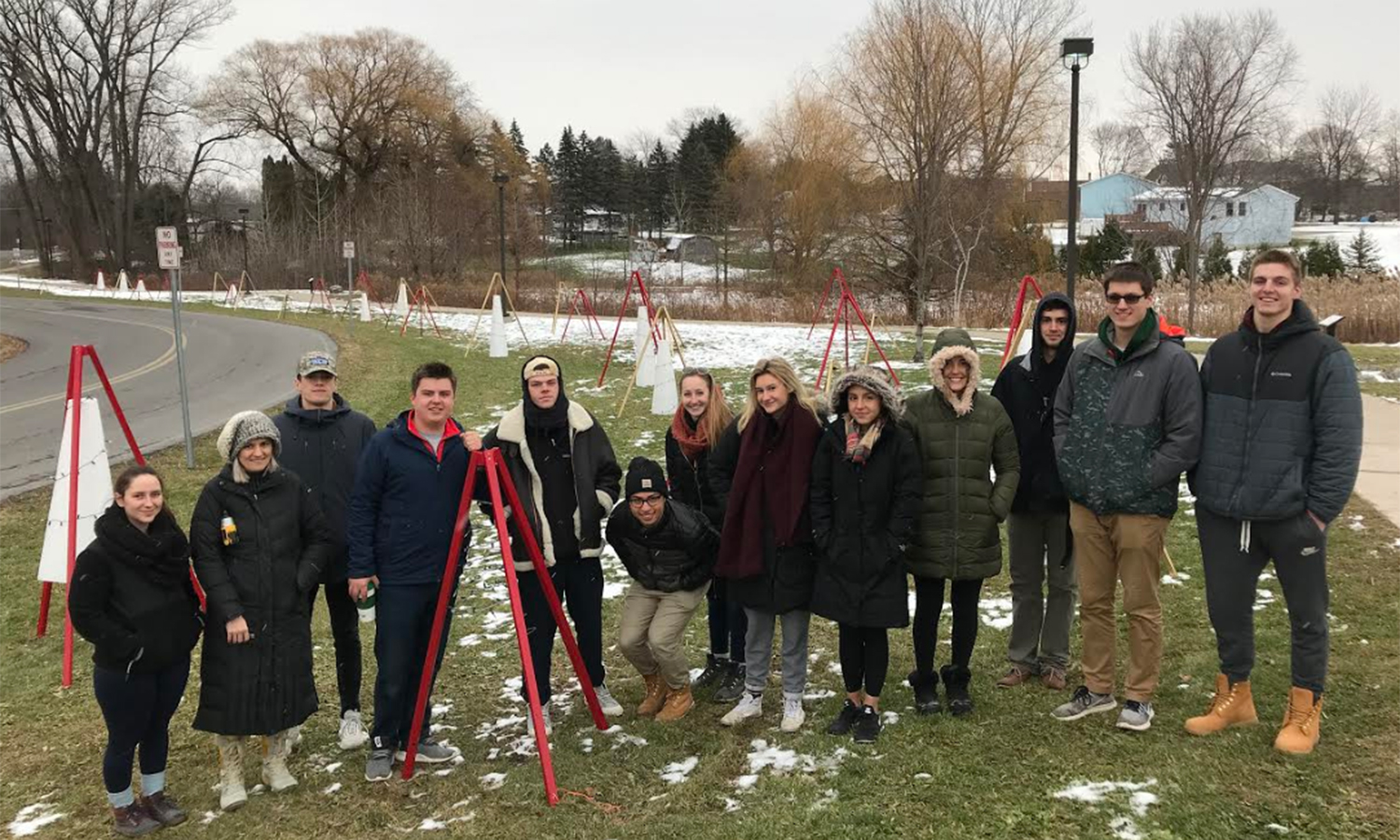 "Students in ""Three Dimensional Design"" with Assistant Professor of Gabriella D'Angelo pose with the holiday installation they designed and built in front of the Geneva Community Center for the Boys and Girls Club Holiday Village. Each hanging conical element carried its own light and power."