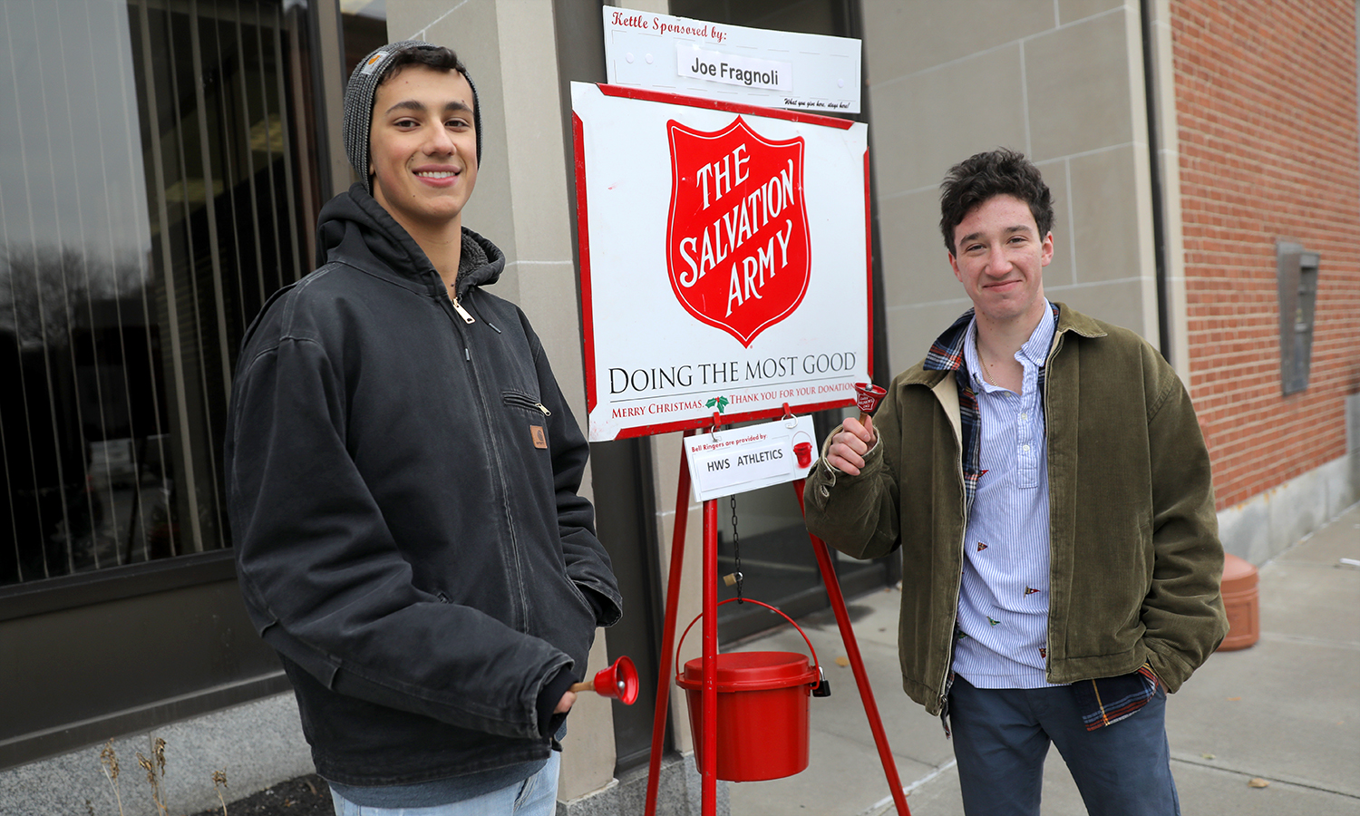 Hobart Cross Country runners Jeremiah Piersante and Max Tulchinsky volunteer as bell ringers for The Salvation Army outside of Community Bank in downtown Geneva.