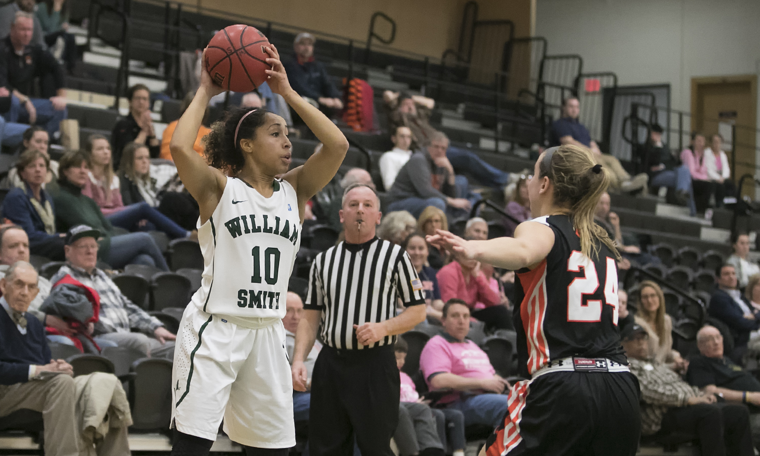 William Smith Junior Kendra Quinn-Moultrie looks for an open teammate in Fridays Liberty League game. The RIT Tigers hot shooting lead them to a 79-50 win over the Herons.