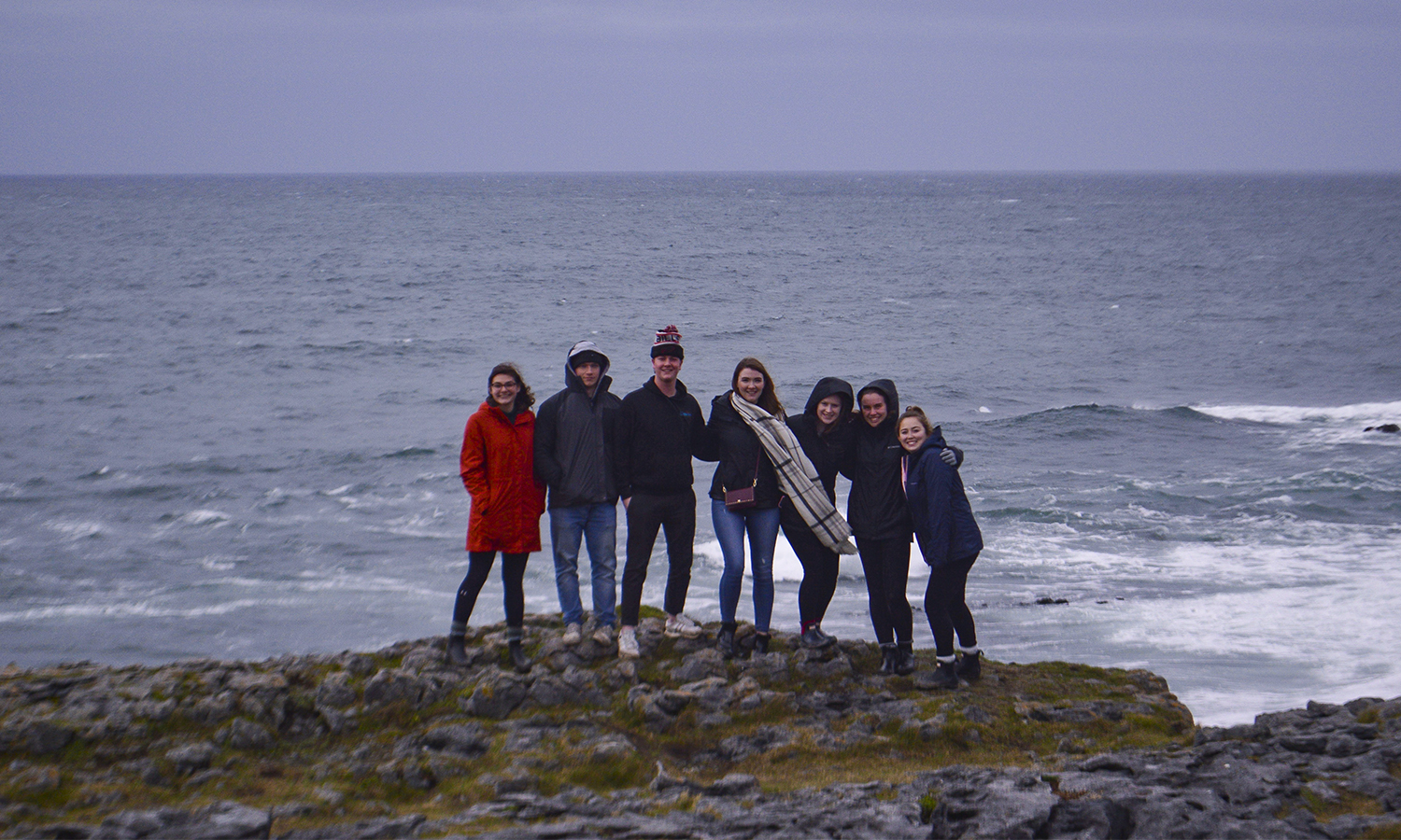 Edie Falk '21, Ryan Carey '20, Dylan McDonald '20, Lindsay Carr '20, Genevieve Carpenter '20, Eileen Rath '20, and Bennett Tierney '20 stand at the Burren National Park on the West Coast of Ireland while abroad in Galway.