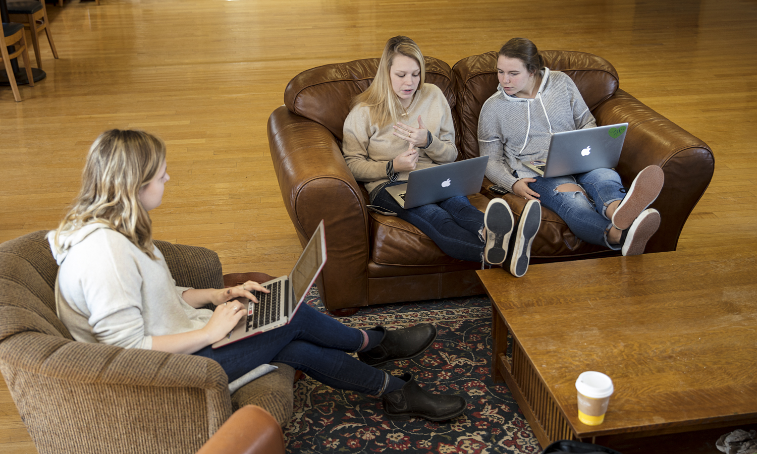 Sasha Carey '18, Molly Bruce and Ellie Cook '18 work on a project for thier Sociology senior seminar with Professor of Anthropology and Sociology Jack Harris.