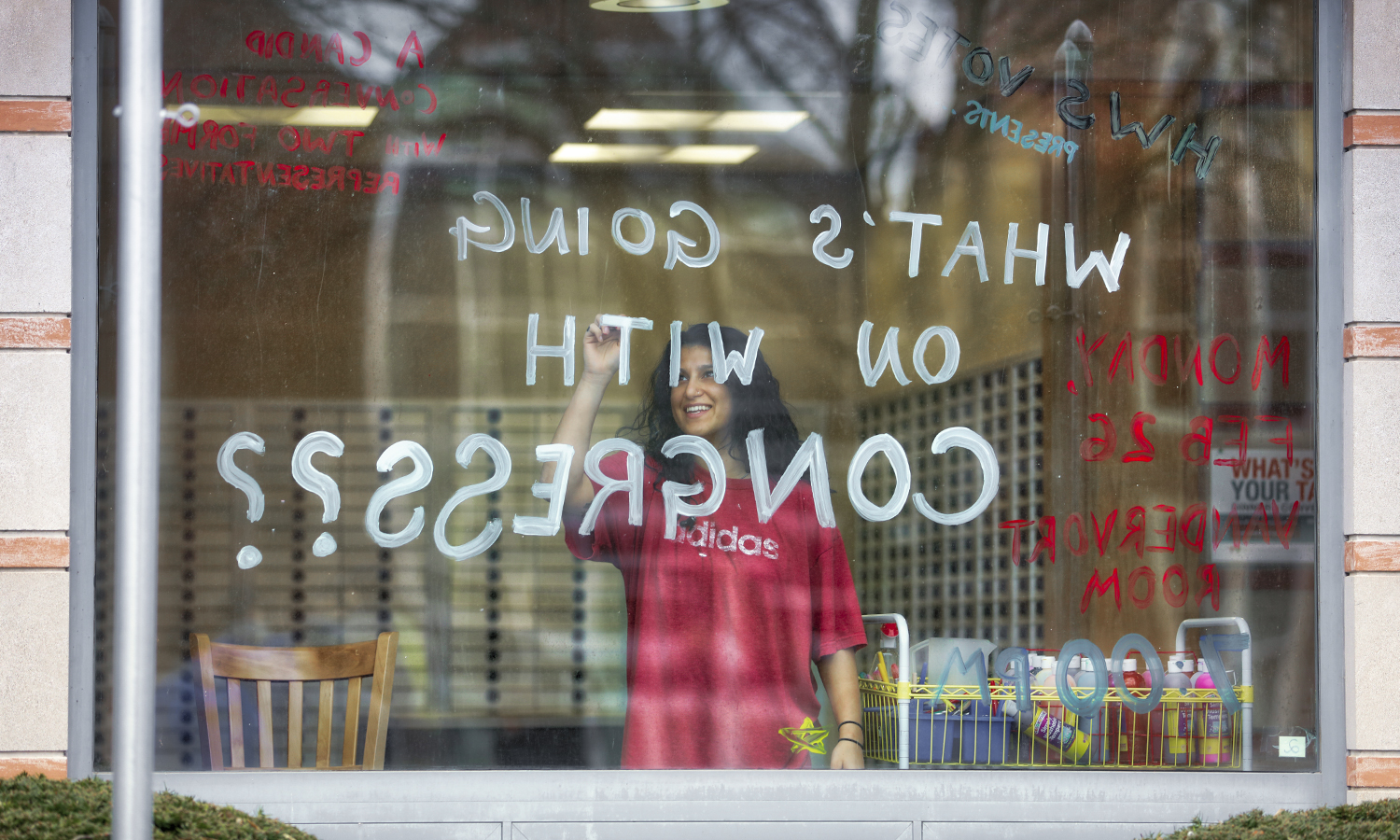 "Divya Tewari '18 paints a window in the Scandling Campus Center to advertise for the ""Congress to Campus"" event on Monday, February 26th."
