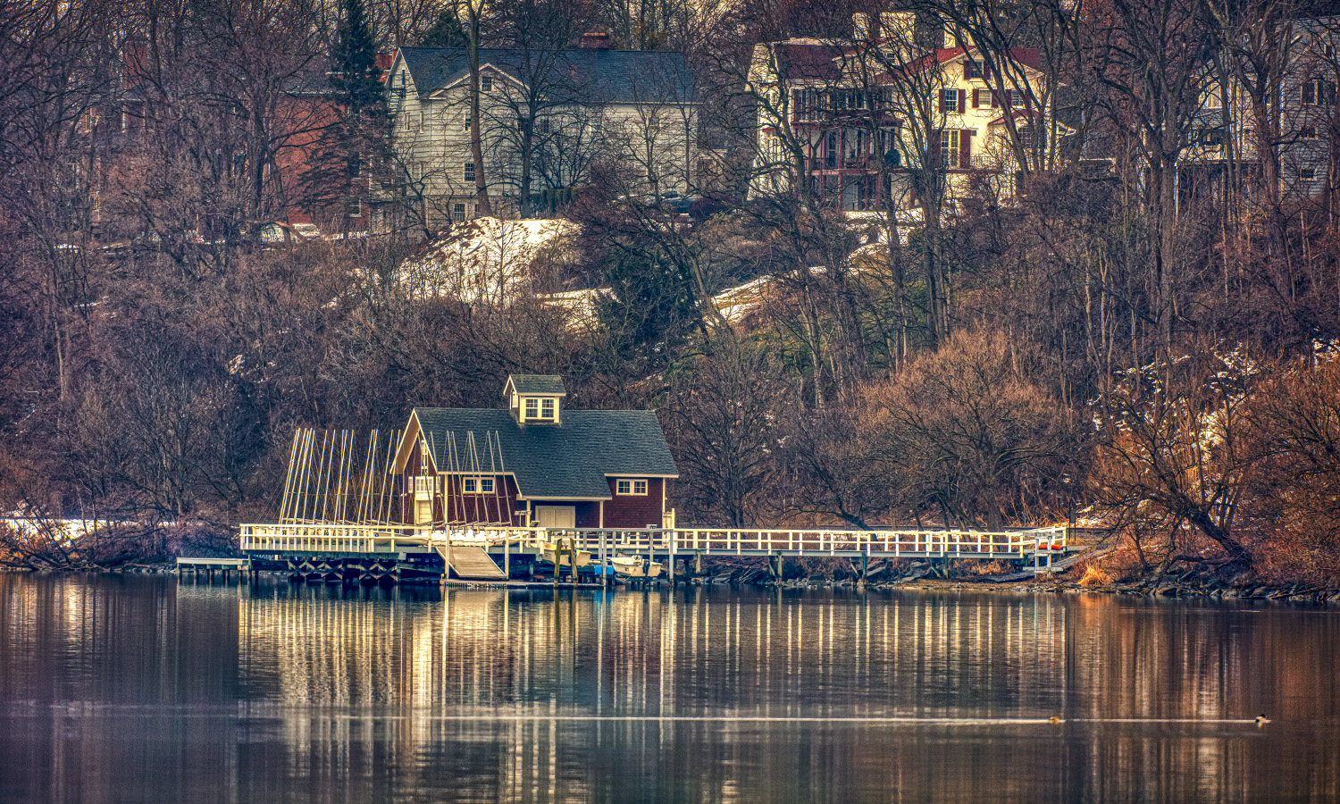 A reflection of the Bozzuto Boathouse shines on Seneca Lake.