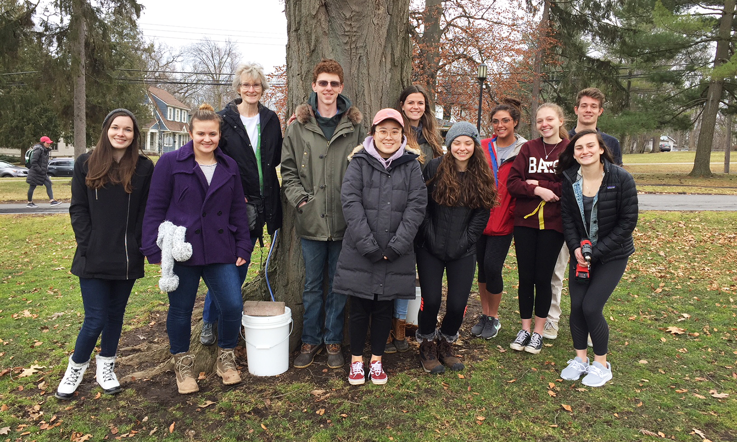 """As part of """"The Biology of Plants"""" with Professor of Biology Elizabeth Newell, students pose for a photo while gathering syrup from a maple tree on William Smith Hill."""