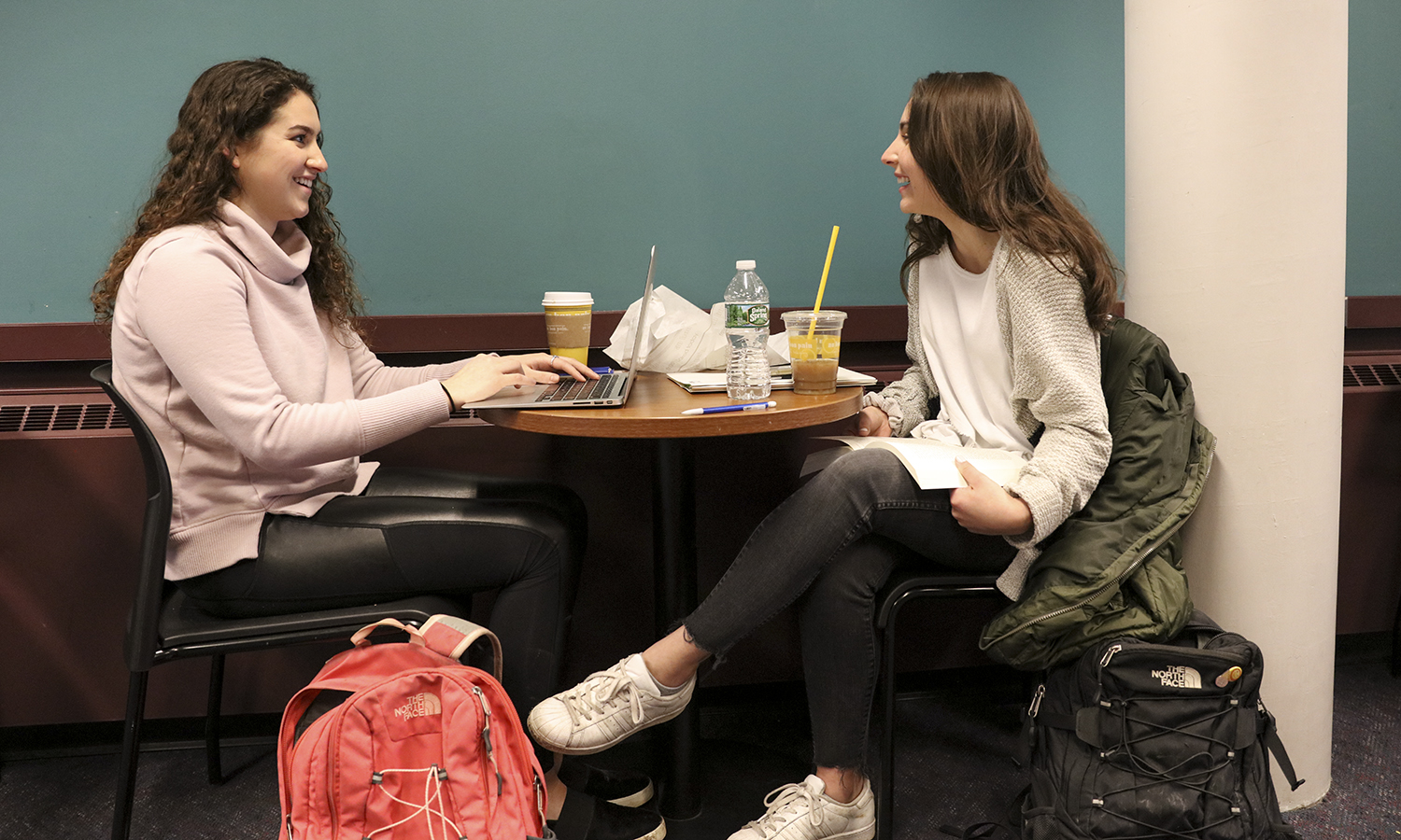 Victoria Vincelette '21 and Nicole Spada '21 chat while working in the Warren Hunting Smith Library.