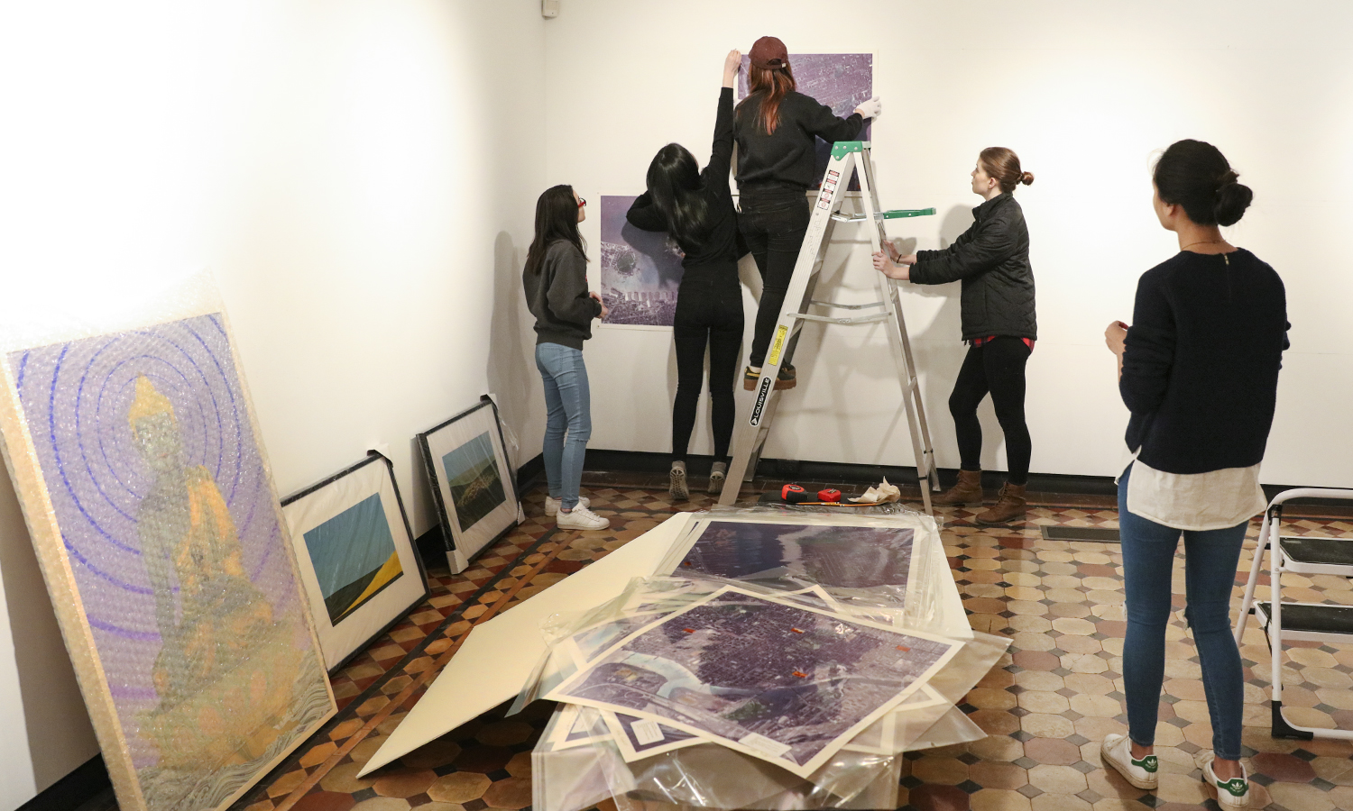 "Students install artwork for the upcoming ""Art for Art"" Exhibit at the Davis Gallery for the Performing Arts. The exhibit celebrates the tenth anniversary of the Davis Galery."