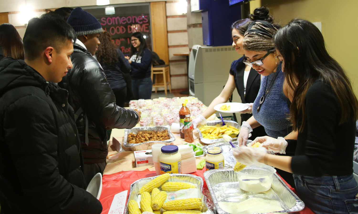 Students enjoy elotes, pastelitos and Mexican candy bags in Scandling Campus Center during the Bodega Fundraiser for the Boys and Girls Club hosted by the Latin American Organization.