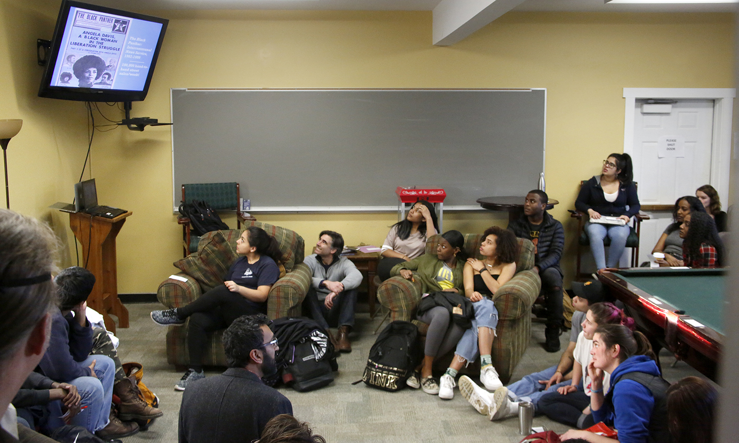 """Associate Professor of Education Khuram Hussain (bottom) leads a discussion on the history of the Black Panter Party during the """"The Black Panther Party: Education and Liberation"""" event in the Office of intercultural affairs."""