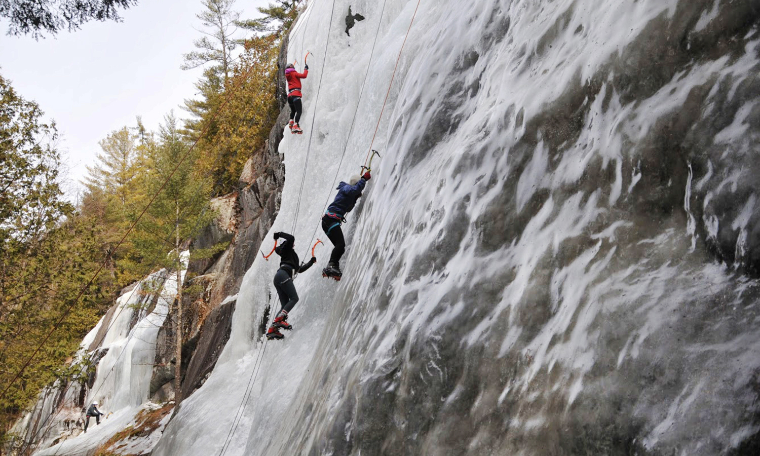 Members of the HWS Outdoor Recreation and Advetnure Program climb a an ice-covered boulder during a trip to the Adirondacks.