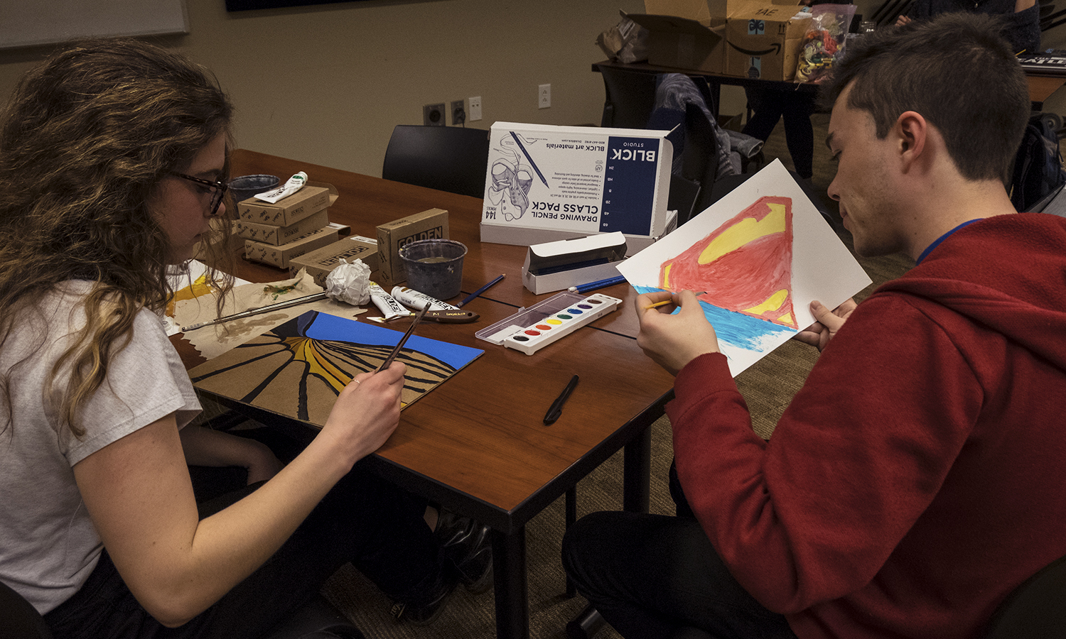 Ainsley Rhodes 'X and Austin Kennie 'X draw during an open student event sponsored by the Art + Design Collective.