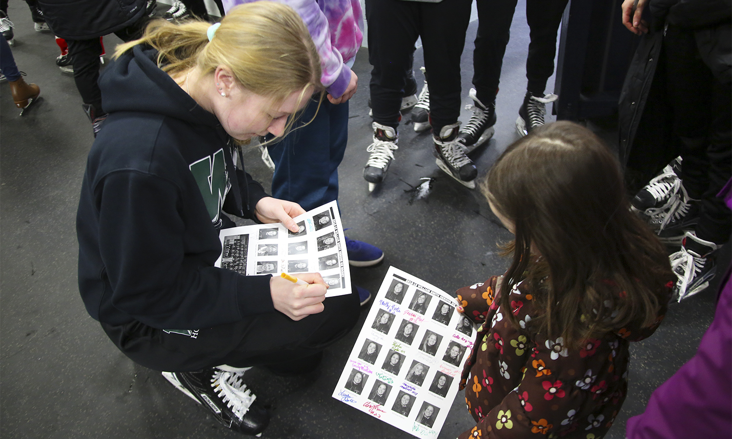 Anna Krajewski '22 meets a fan and signs her photo on the William Smith Ice Hockey roster after Community Skate.