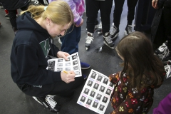 Anna Krajewski â22 meets a fan and signs her photo on the William Smith Ice Hockey roster after Community Skate.