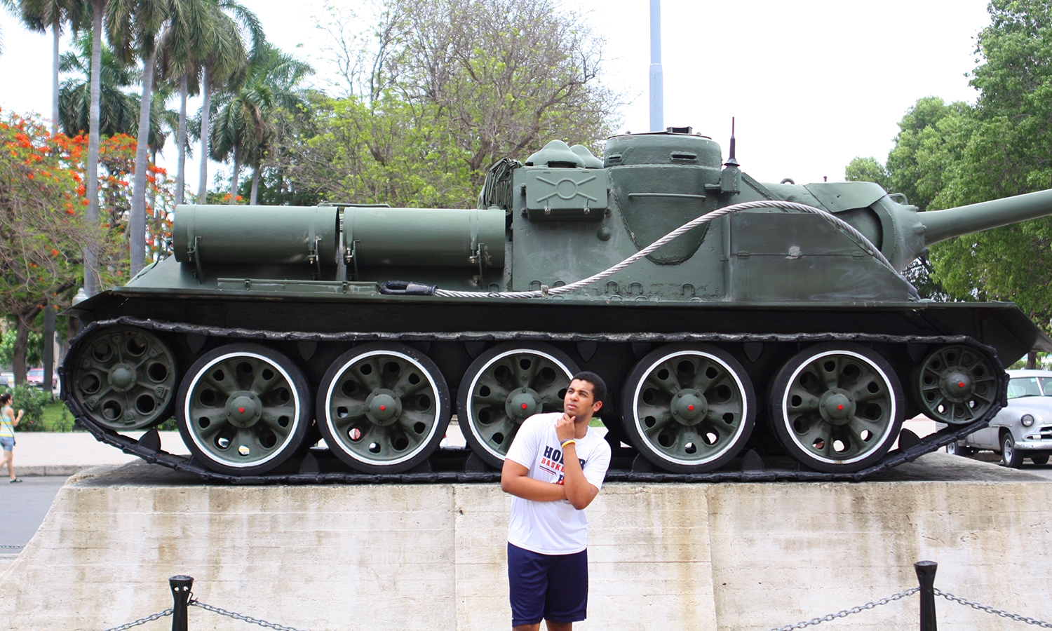 Isaiah Young '18 poses with a military tank at the Granma Boat Memorial.