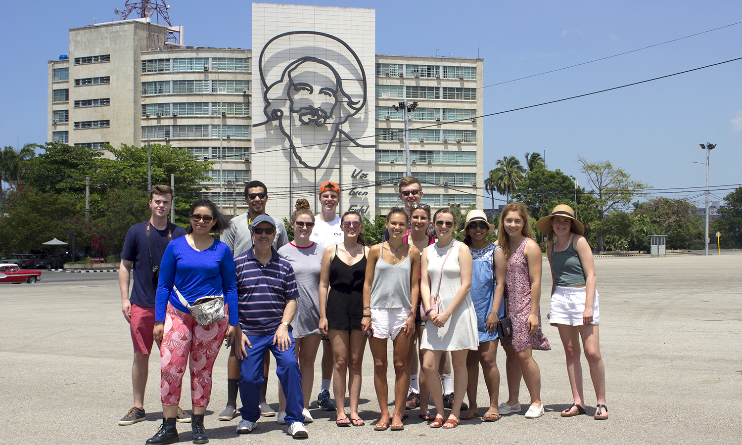 The group poses in front of the Ministry of Informatics and Communications building at the Plaza de la Revolución. Pictured on the building is Camilo Cienfuegos, a Cuban revolutionary.