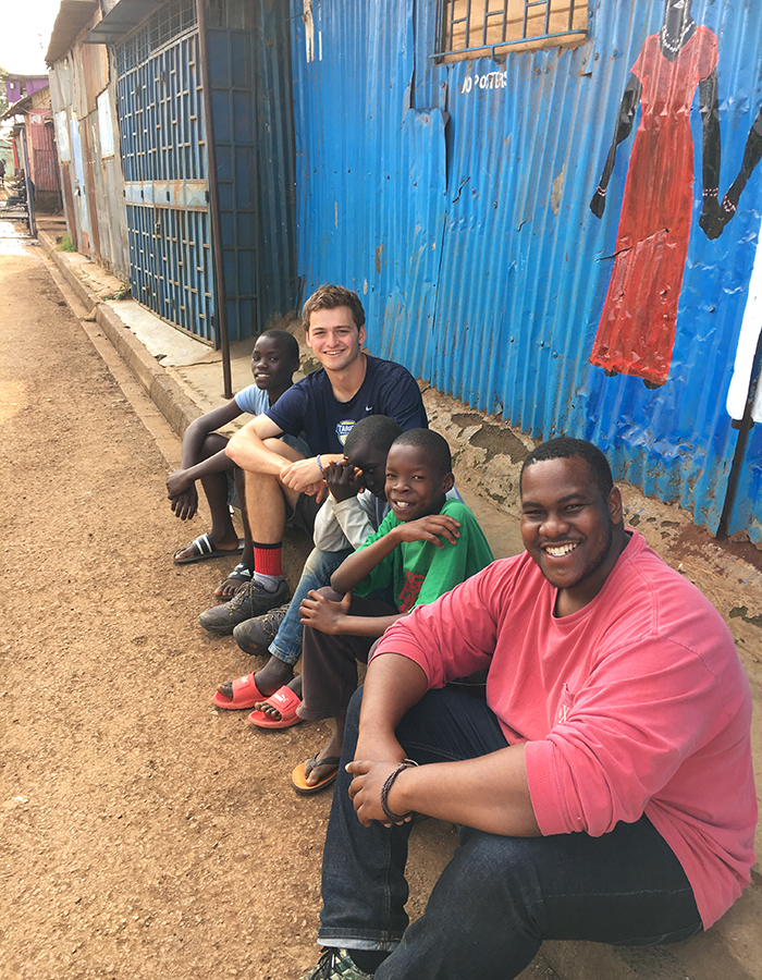 Sam Eaton 'X and Josiah Bramble '19 gather for a photo with local children on the streets of Nairobi, Kenya.