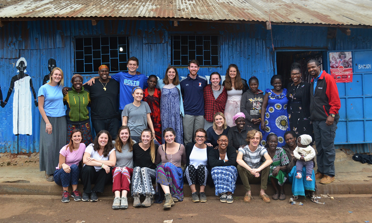 Students gather for a photo with members of the The Power Women, a group of 15 women in Nairobi, Kenya who work to reduce the stigma surrounding HIV and reduce poverty in in their community of Kibera.