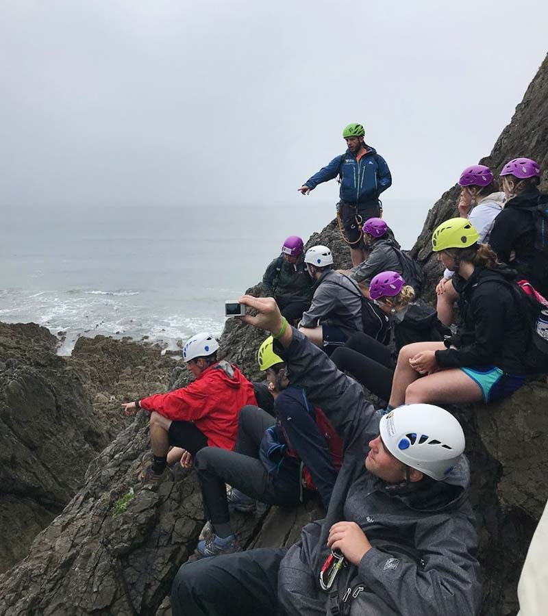 The group discusses climbing routes and safety techniques as they prepare for a guided climb to to Paviland Cave.
