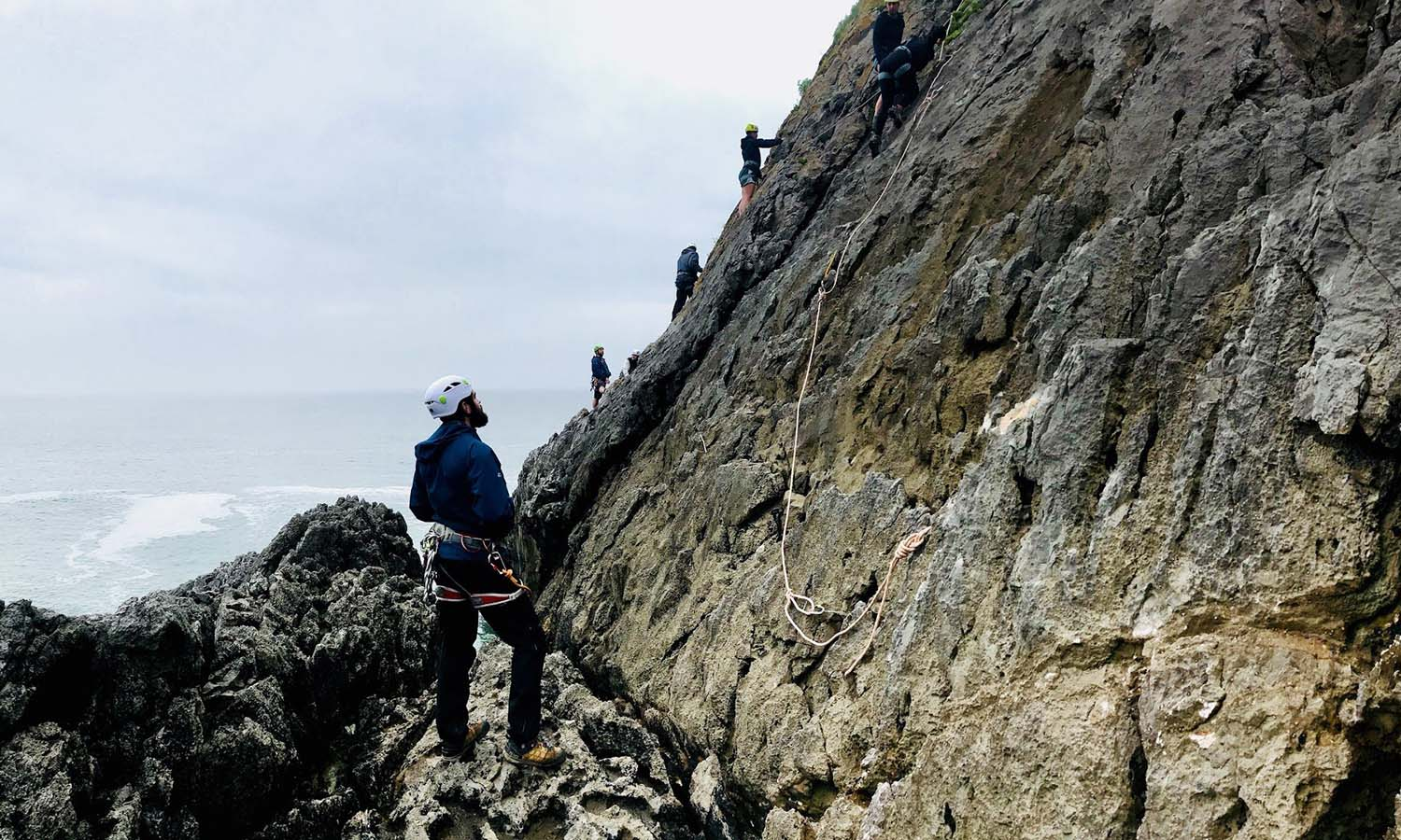 Participants of the Wales program work together to cross the ocean cliffs on their journey to Paviland Cave.