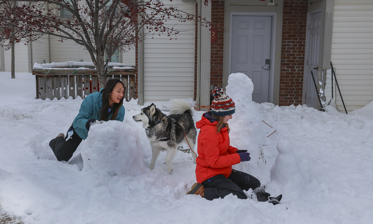 Denali Minnick '19 and Therese Kowalczyk '19 build snow people with husky Ace.