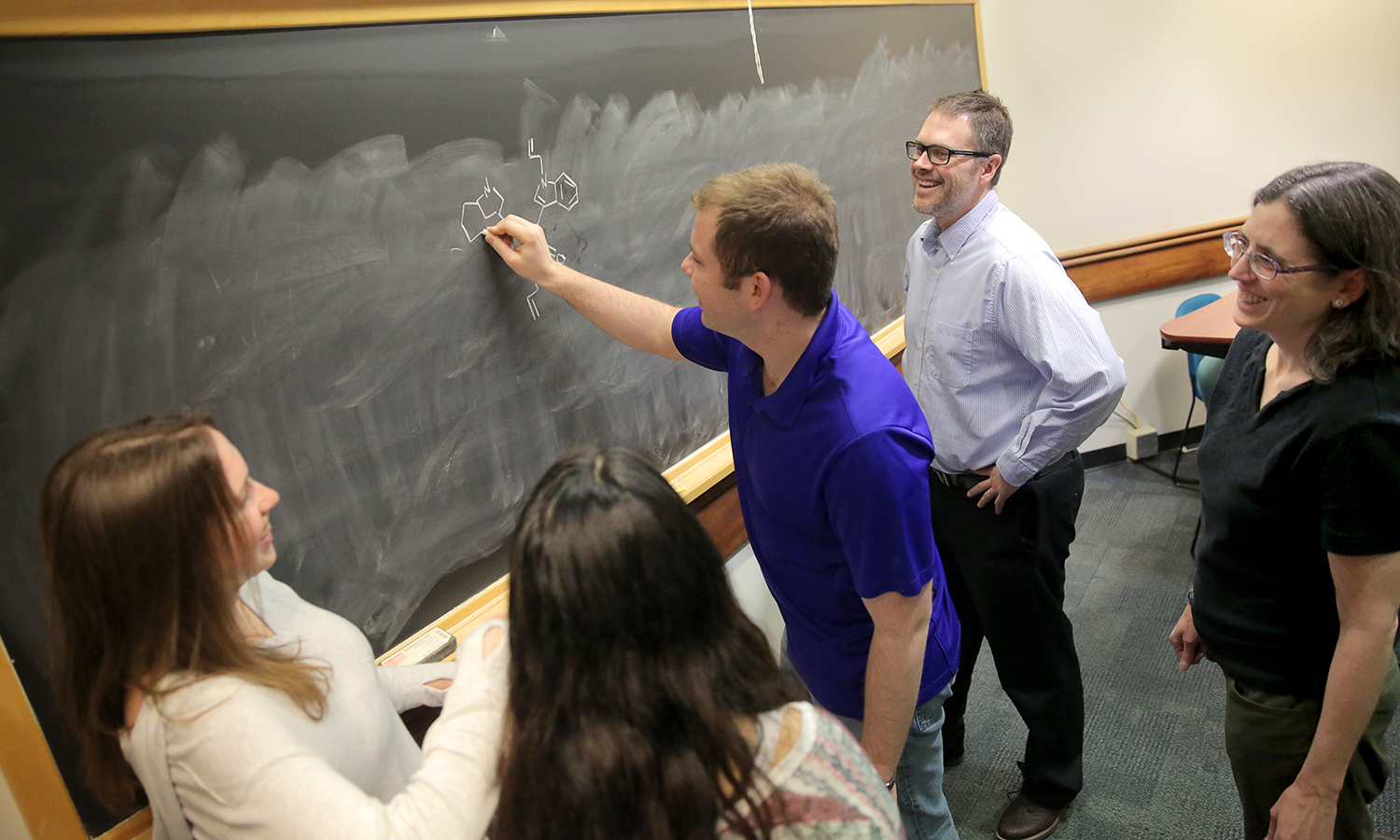 Professor of Chemistry Erin Pelkey and Associate Professor of Biology Patricia Mowery look on asNathanyal Truax '17 draws a molecular diagram for a bisindole–pyrrolidinone conjugate, whichiTraux is researching for his honors thesis on the synthesis of indole-containing small molecules with potential anti-cancer activity.