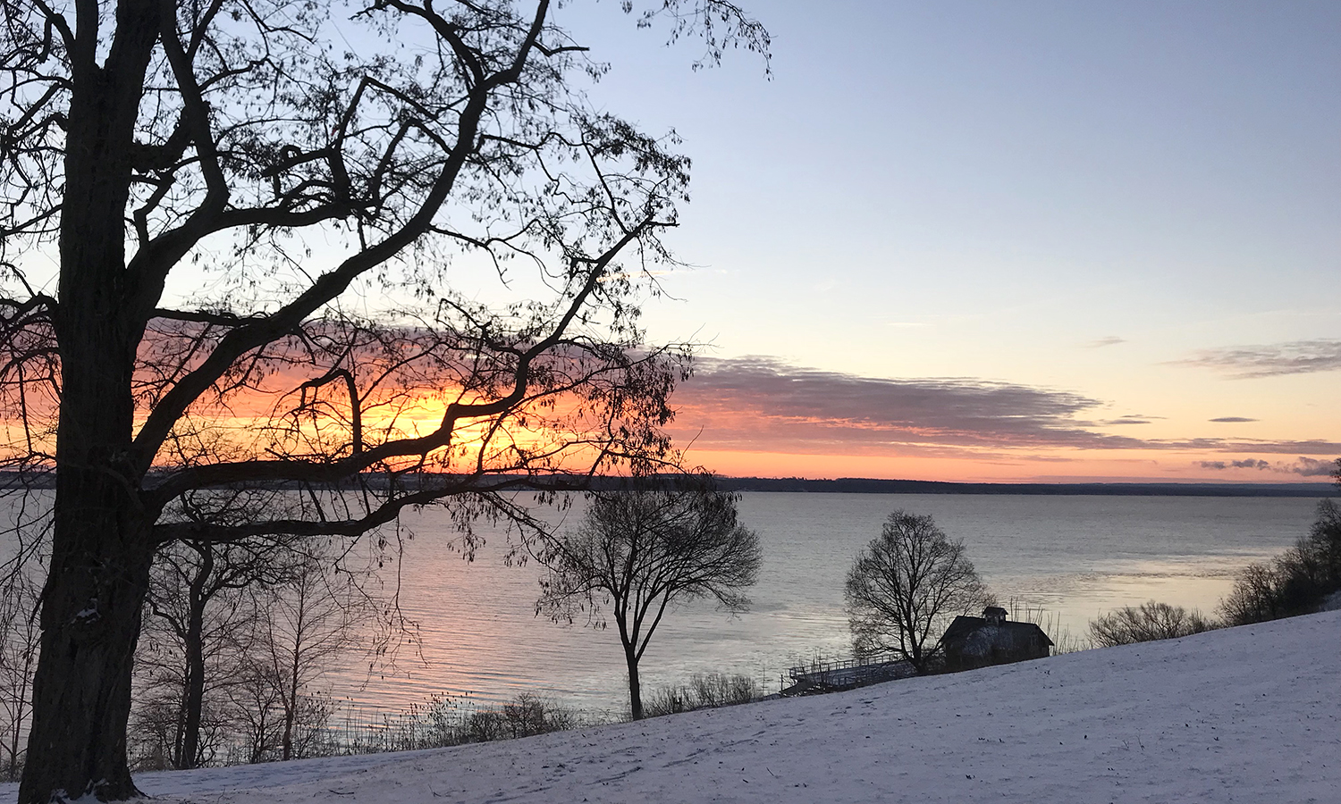 The horizon glows as the sun rises over Seneca Lake.