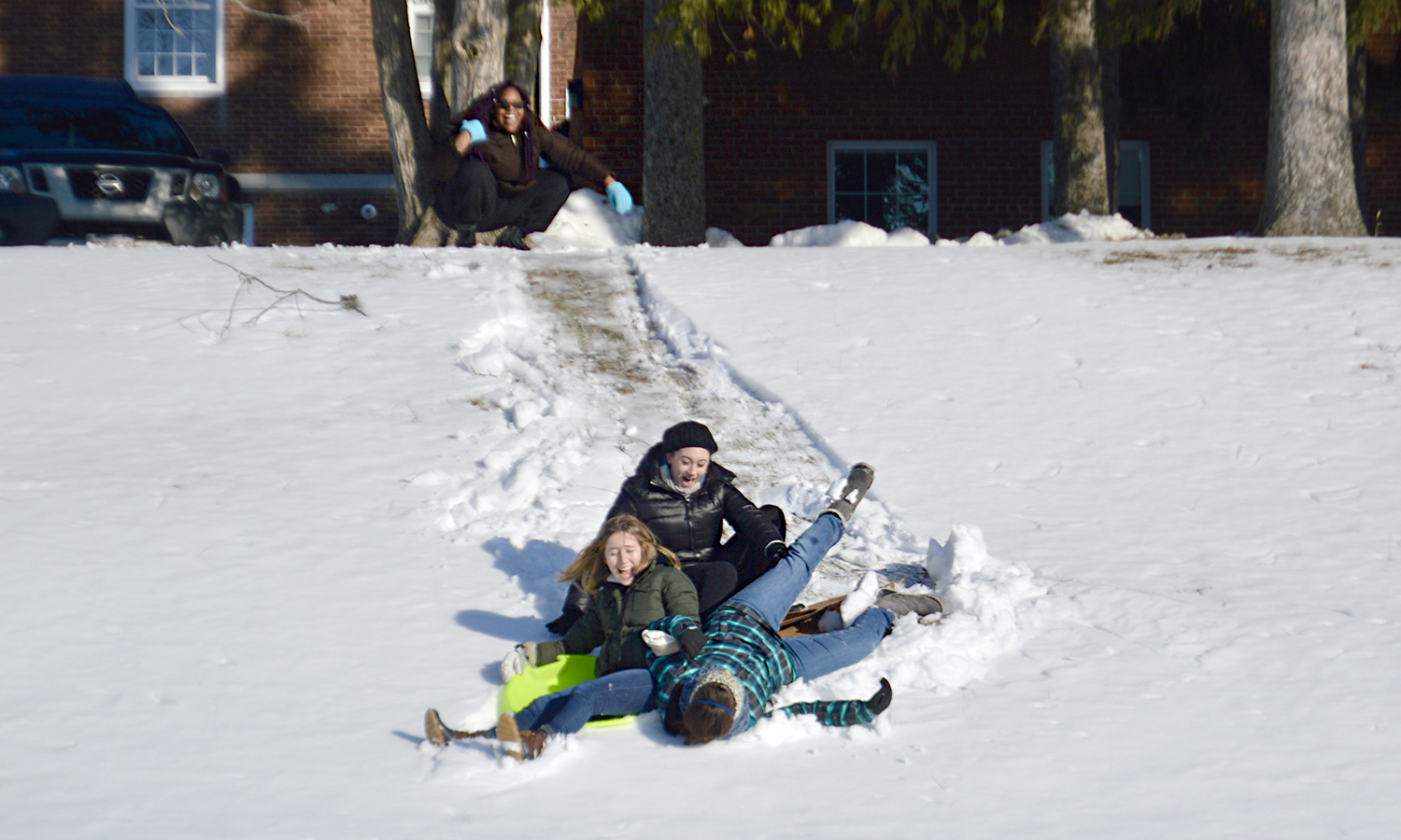 Bernice Shed '20 (top left) watches as Addison Gilbard '20, Hannah Bini '20 and Alex Curtis '20 sledding down the hill behind Comstock Hall.