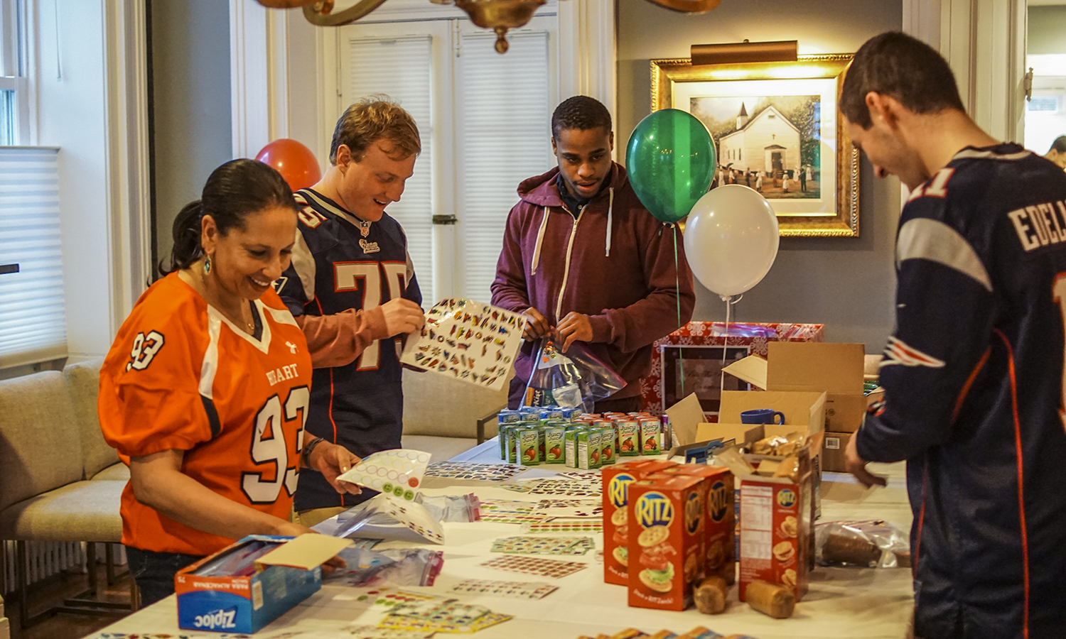 Kim Wilson Vincent HON '21, Ryan Montbleau 'X, Taner Bennerson 'X and Josh Wasserman 'X assemble snack packages for new HWS Food Pantry at the President's House on Thursday.