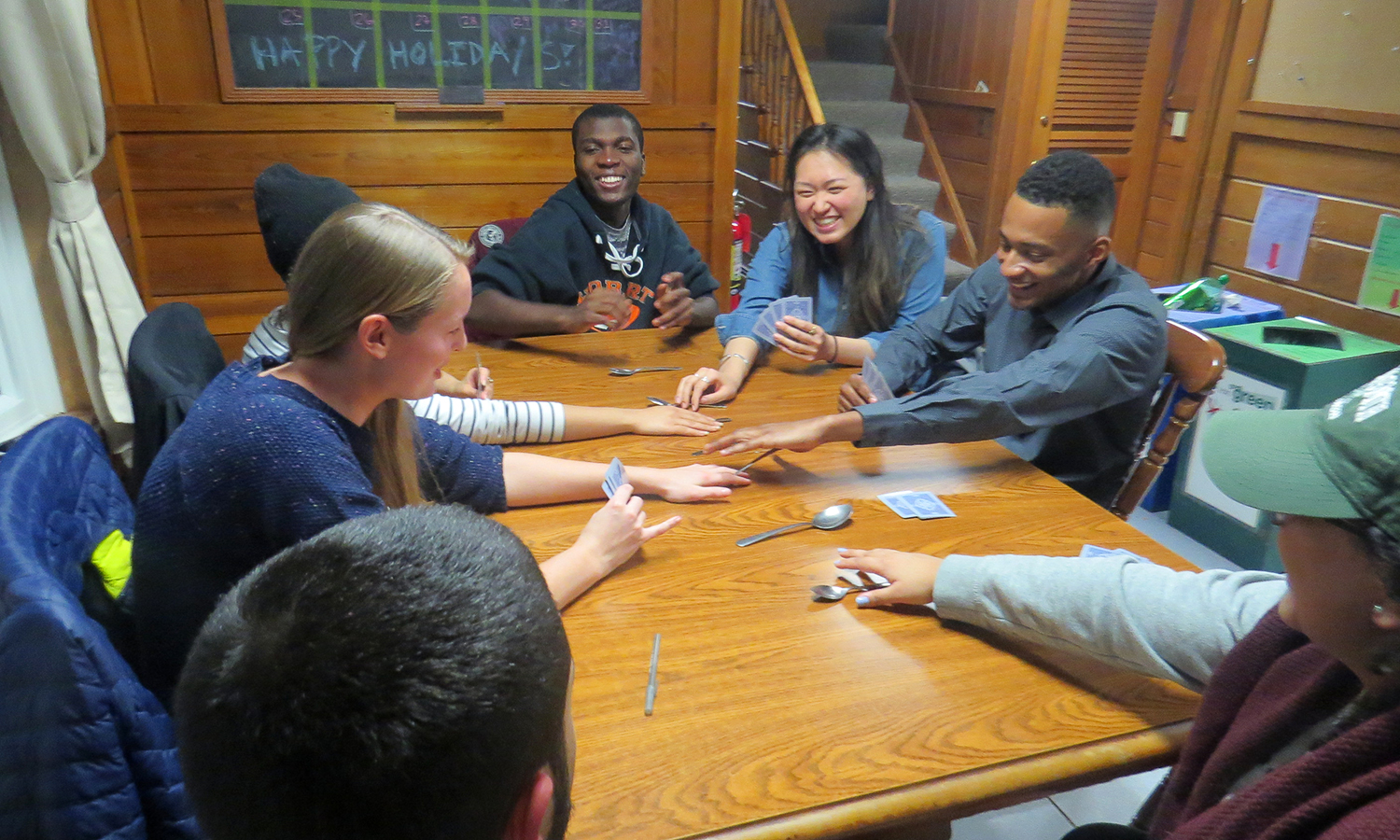 "Students play a game of ""spoons"" during the ""Winter Break Sushi & Pizza Night"" event at the Intercultural Affairs House."