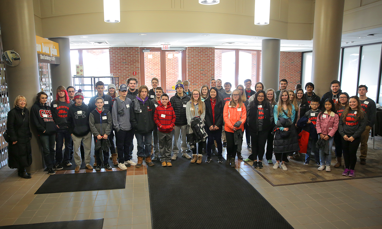 Members of Geneva Heroes gather for a group photo in the atrium of Warren Hunting Smith Library.