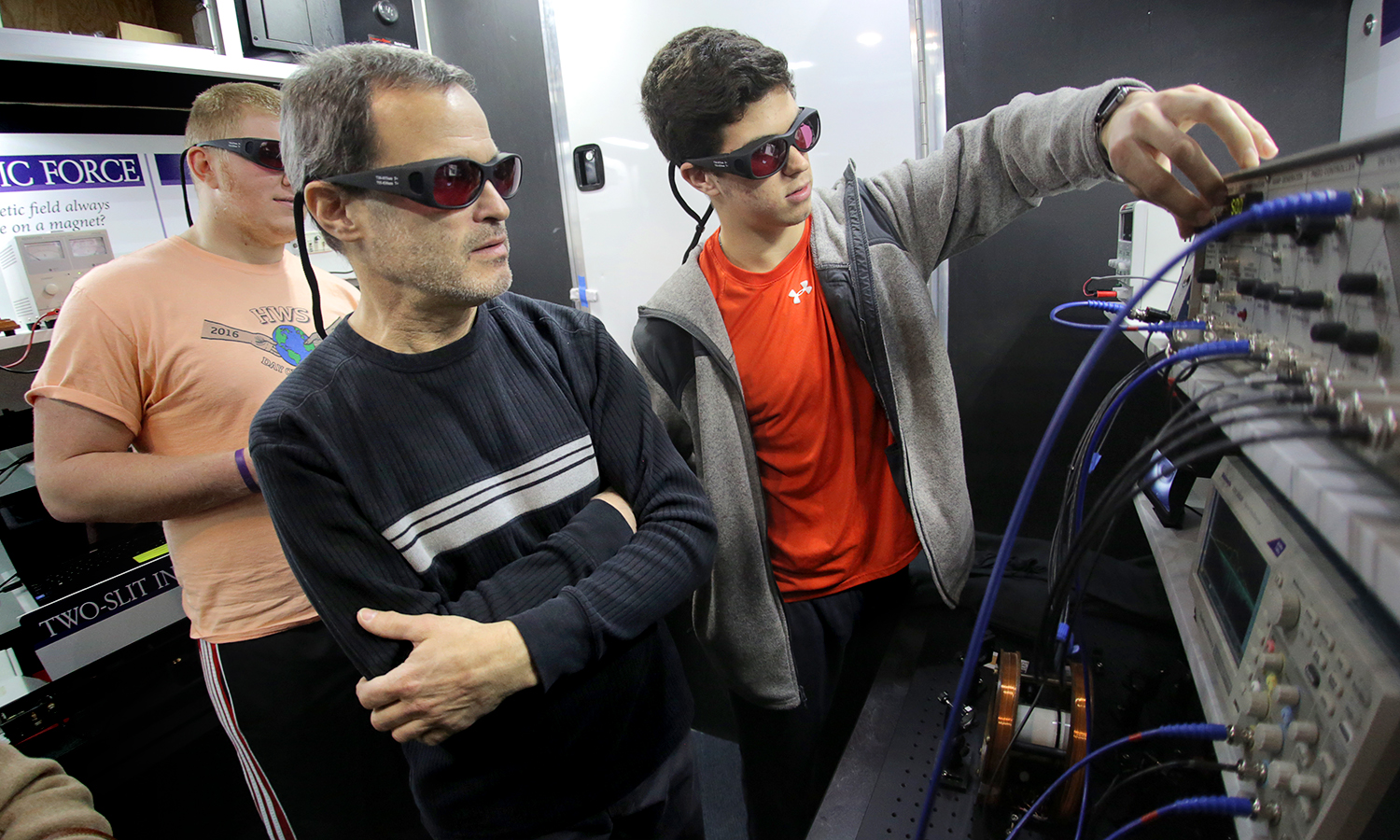 """Kyle Grimaldi â19 experiments with a diode laser spectroscopy, a tool that allows students to observe saturated absorption of rubidium gas, with during the """"Food Truck for the Physics Mind"""" event on Tuesday."""
