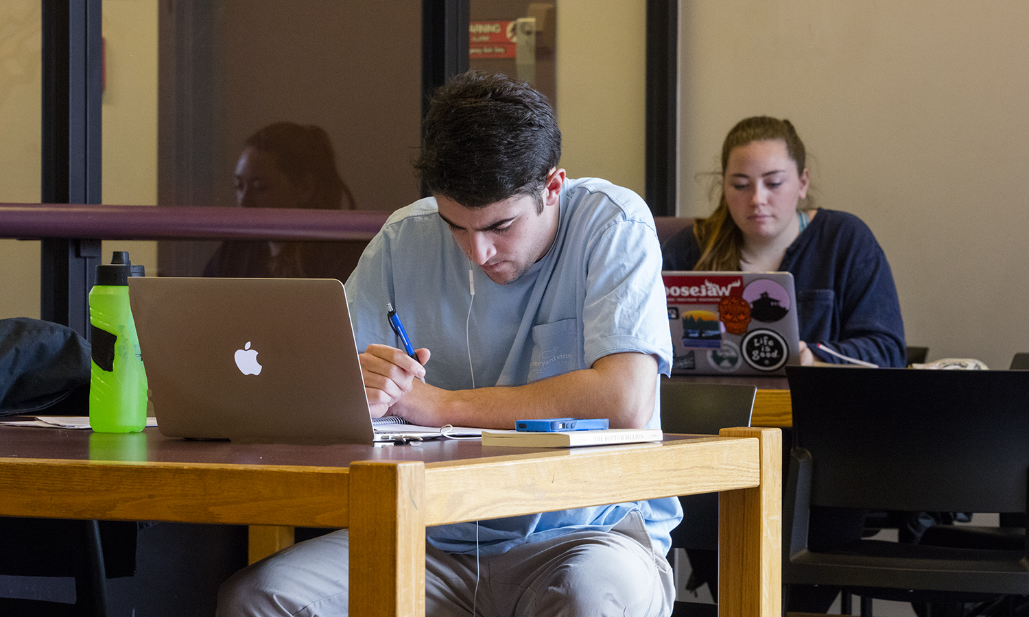 """Charlie Thompson â18 works on an assignment for """"Economics of Inequality and Distribution"""" with Assistant Professor of Economics Joshua Greestien."""