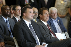 New York Governor Andrew Cuomo sits with Geneva City Manager Matt Horn and other members of the Geneva City Counsel and listen to Senator Michael Nozzolio address the attendees, including Hobart Parent Mark Grambling.