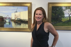 Amber Waterhouse '89 poses in front of two of her oil paintings at the Dolphin Gallery of Hingham Public Library in Hingham, MA, which will host her work from July 2nd to July 28th.