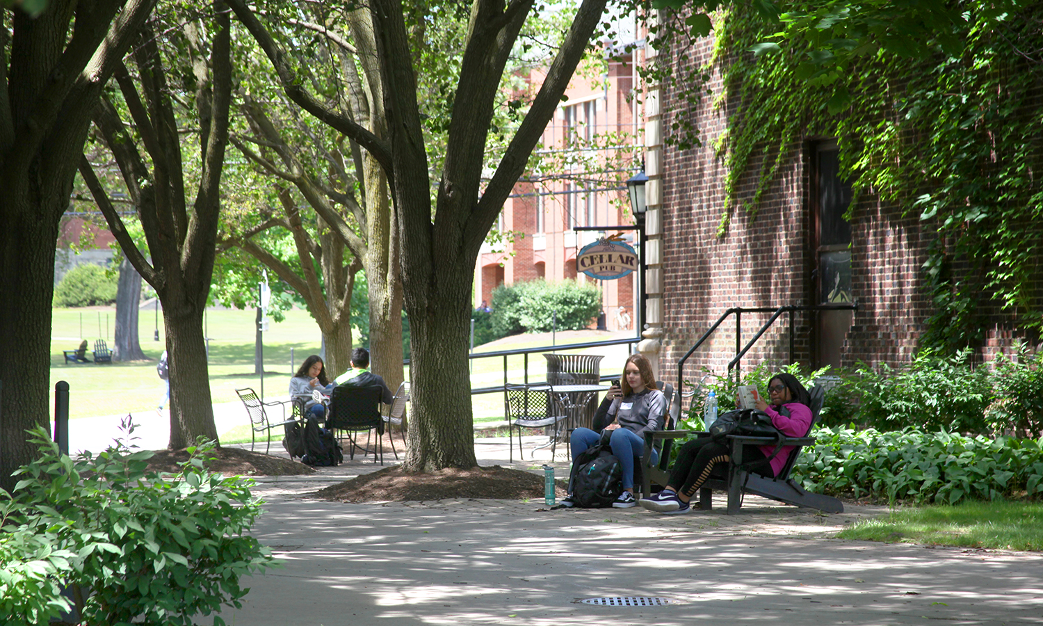 Students participating in the HWS Summer Academy enjoy the sunshine on the patio outside of Coxe Hall.