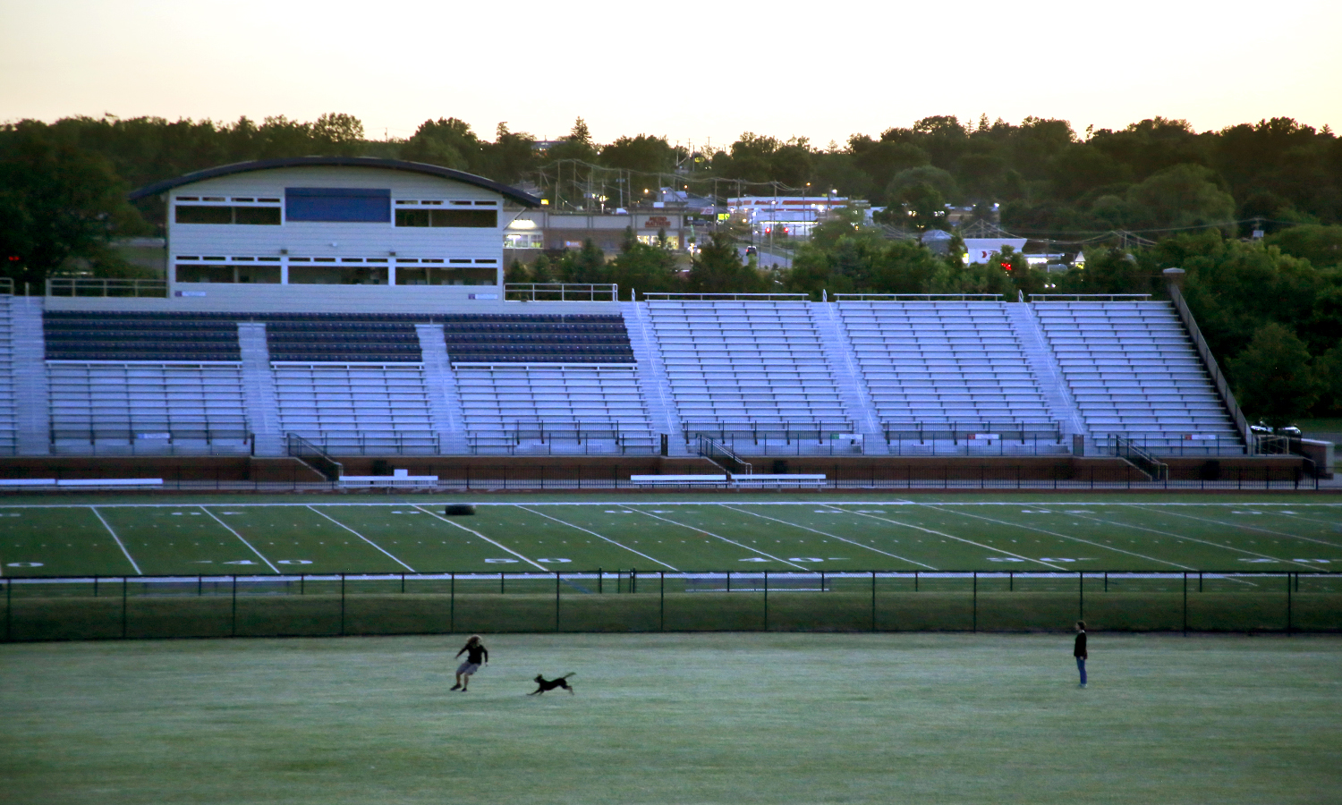 Students play with a puppy outside of Boswell Field.
