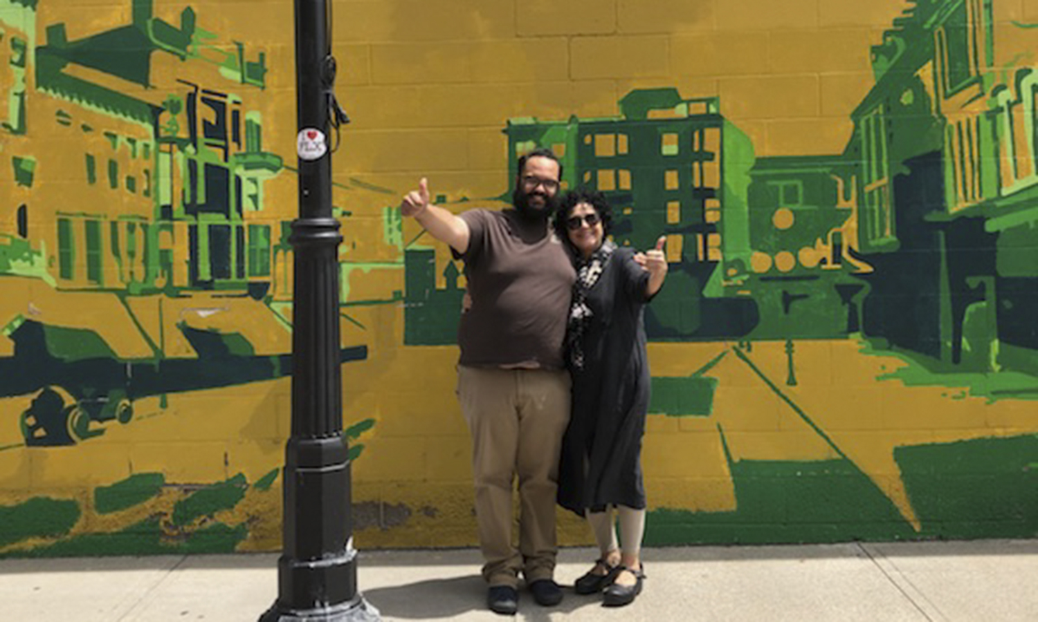 Director of Intercultural Affairs Alejandra Molina (right) and Pablo Modesto '09 gather for a photo in downtown Geneva. The mural was painted by Victor  Pultinas '09.