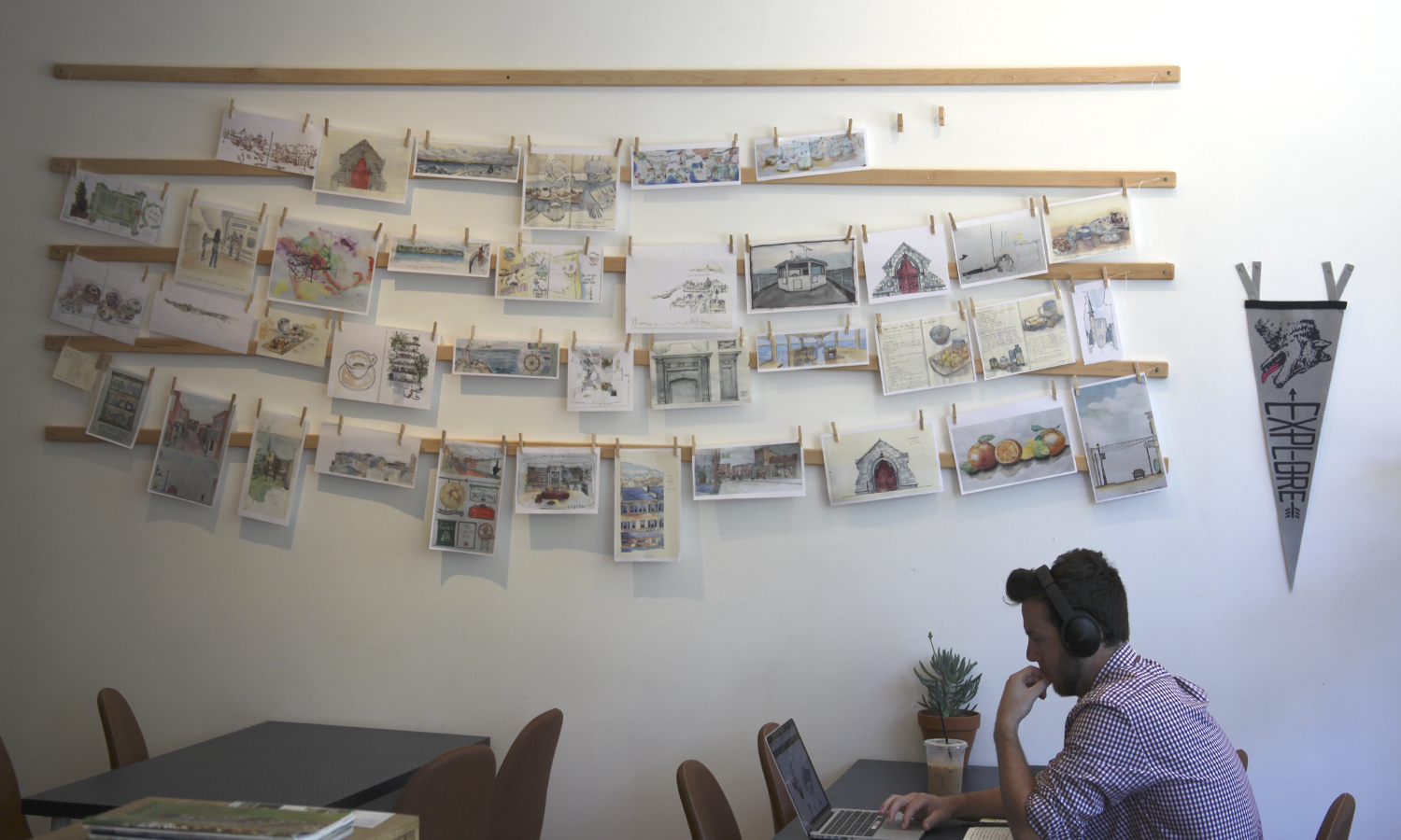 """Orientation Coordinator Tanner Arnold '19 prepares for ithe incoming Classes of 2022's arrival at Monaco's Coffee in Geneva, N.Y. The sketches on display were drawn by students in ARCS 202: """"Watercolor Sketching"""" with Associate Professor of Art and Architecture Kirin Makker."""