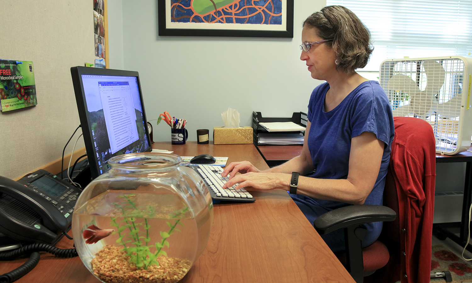 """Associate Professor of Biology Patricia Mowery and her fish """"Finn"""" prepare for summer research in Lansing Hall."""