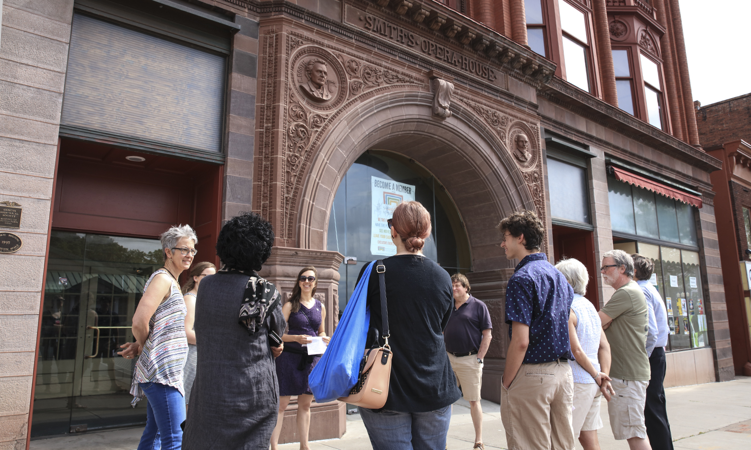 "Associate Professor of Theatre Chris Woodworth greets HWS and Geneva community members before a tour of the Smith Opera House in downtown Geneva, N.Y. Woodworth is currently working with summer research assistants Margaret ""Gretty"" Hollister 'X and Austin Jennings 'X to perform a historical study of the Smith Opera House in honor of its 125th anniversary."