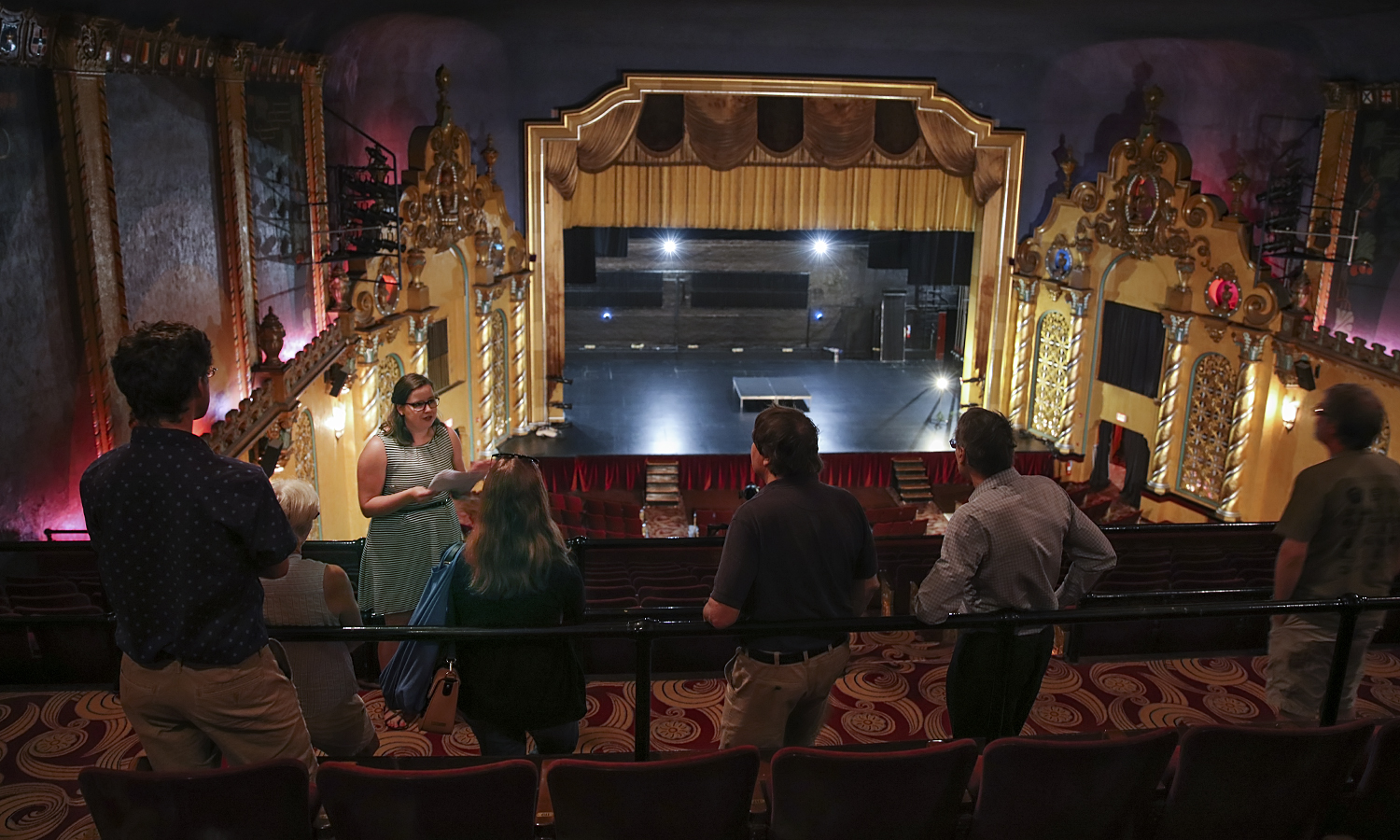 """Summer research assistant Margaret """"Gretty"""" Hollister explains the design history and construction of the interior of the Smith Opera House during a tour."""