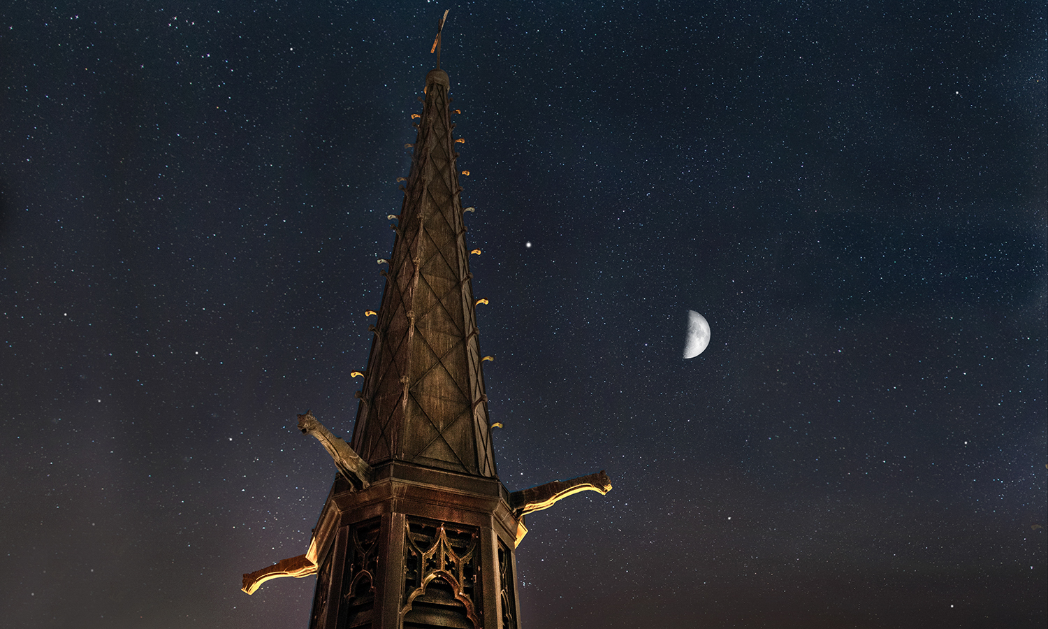 A half moon shines above St. Mark's Tower.