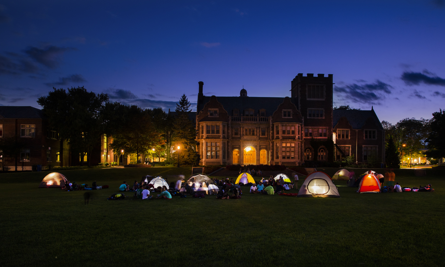 Tent lights illuminate the Quad during a Pre-Orientation Adventure Program campout on campus.