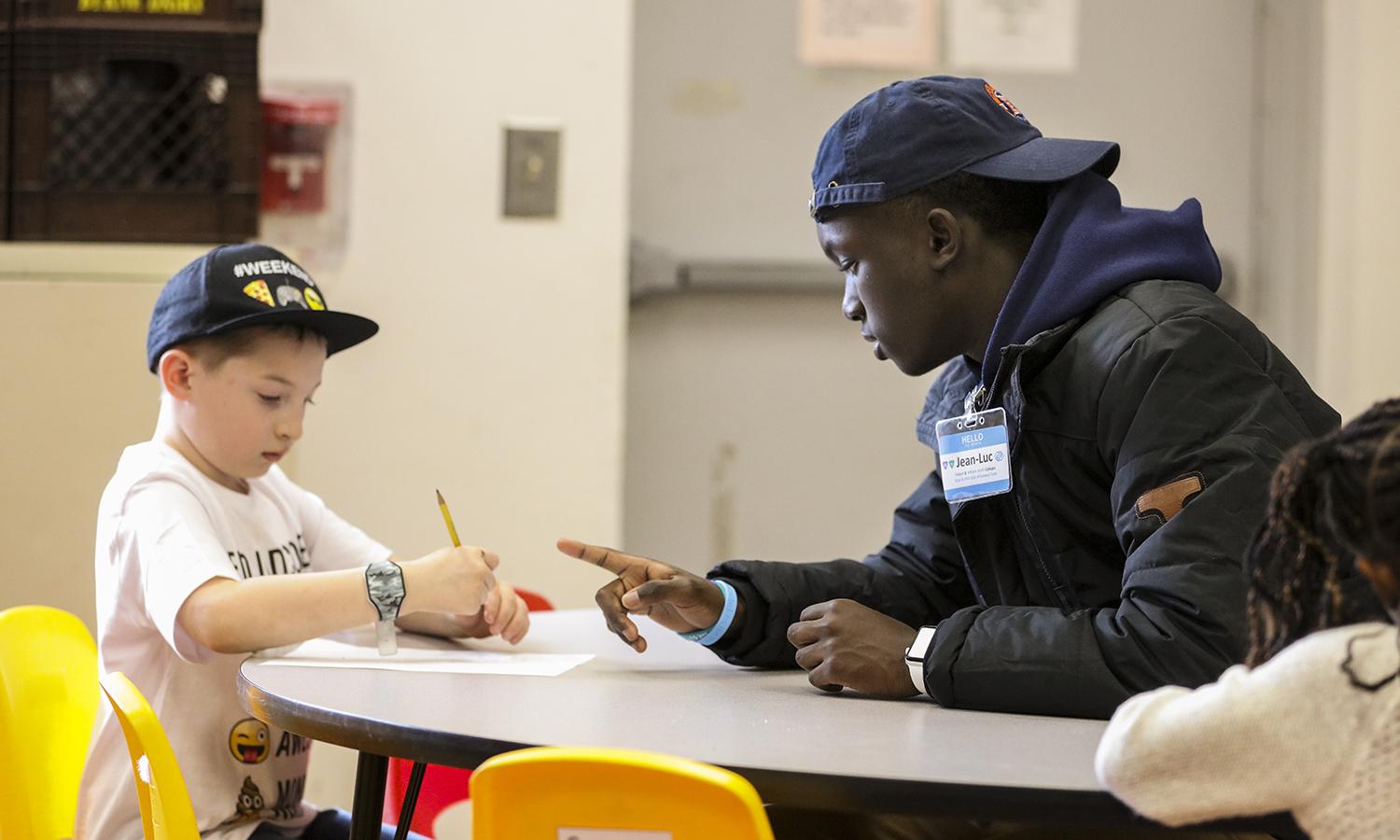 Jean-Luc Shyaka '21 helps a student with his homework after school at the Boys and Girls Club.