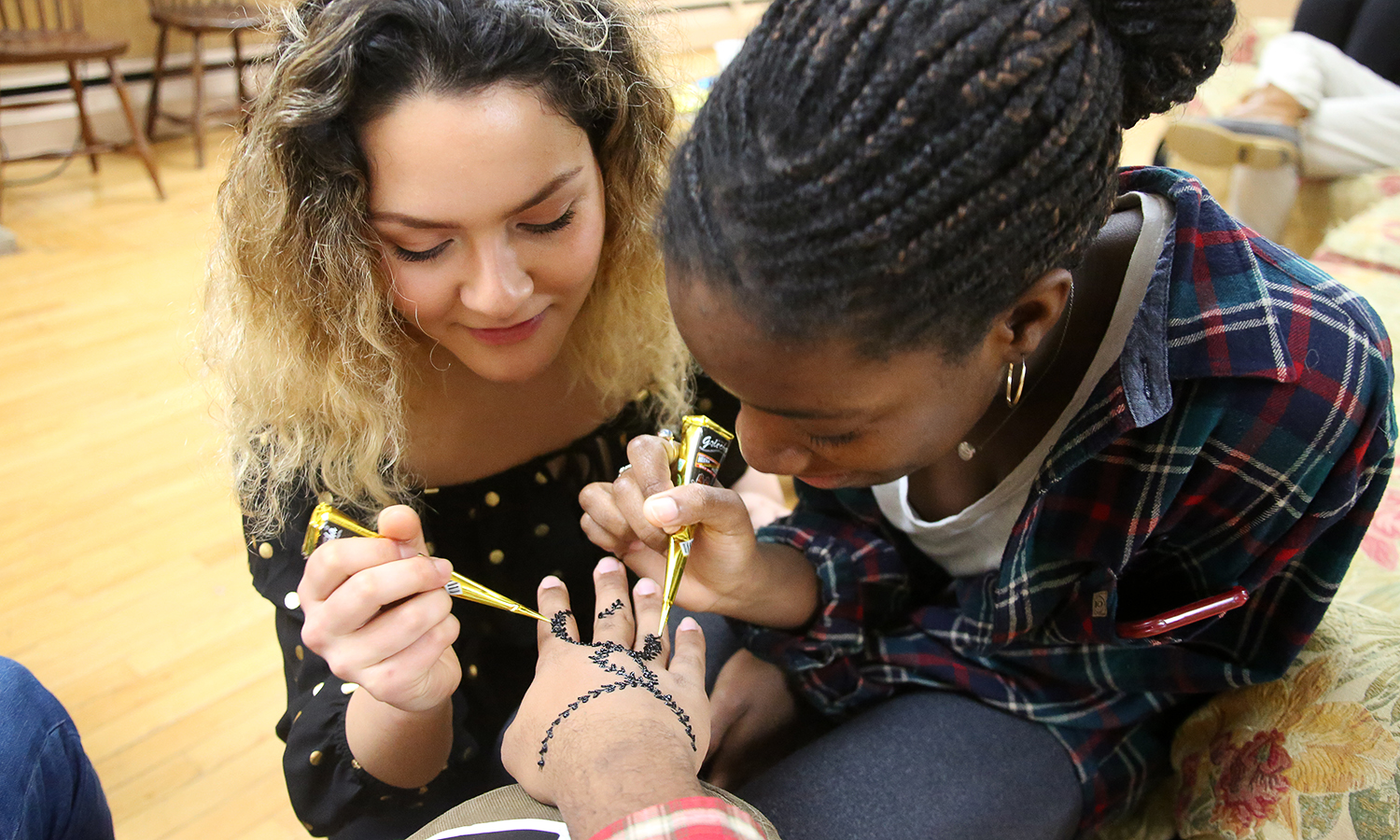 "Nagina Ahmadi '20 and Davida Eyam-Ozung '20 create henna tattoos during ""Henna Night and Dinner"" hosted by the International Student Association in the Hirshson Ballroom."