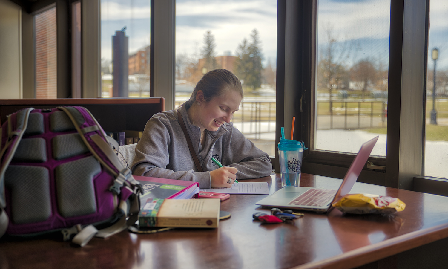"""In Warren Hunting Smith Library, Erica Oosterhoff '18 works on her senior thesis focused on prion disease and neurodegeneration for Assistant Professor of Chemistry Kristin Slade's """"Biochemistry"""" class."""