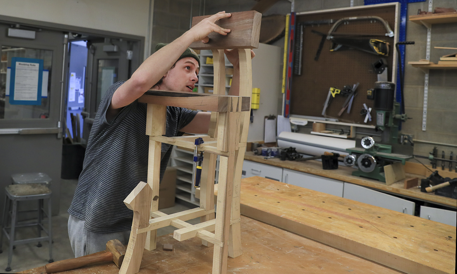 """Zach Felder '18 puts the finishing touches on a stool for guitar playing as part of """"Furniture Design"""" with   Visiting Assistant Professor of Art and Architecture Patrick Kana '12."""