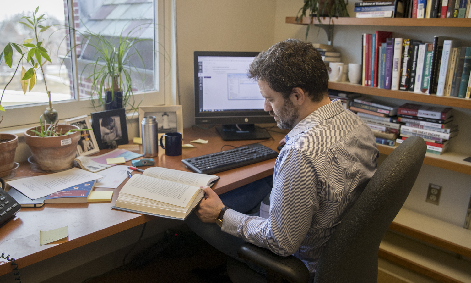 Assistant Professor of Economics Joshua Greensteinworks on his class curriculum in his office in Stern Hall.