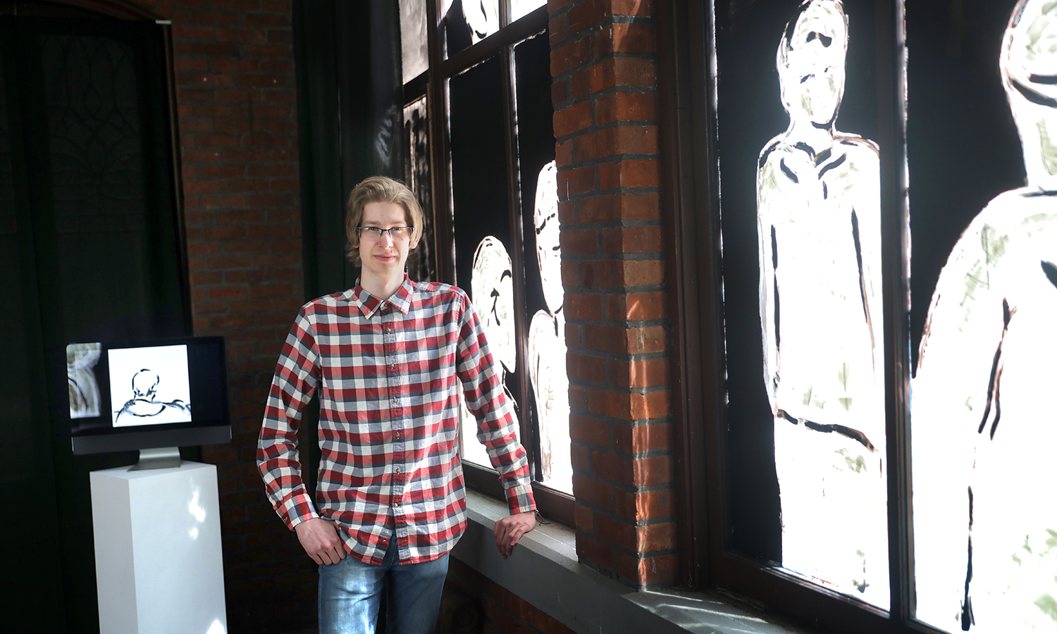 "Jared Ratzel '18 poses with an exhibition of his work, ""Eine Andere Stille"" on display in the Solarium Gallery. Ratzel's exhibit is the culmination of a year-long honors project on the subject of queer German cinema."